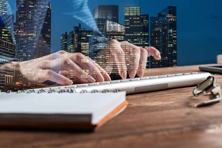 Real estate investment company double exposure concept with skyscrapers. Business lady working with computer in office. Financial specialist working at workplace. Accounting and project management.