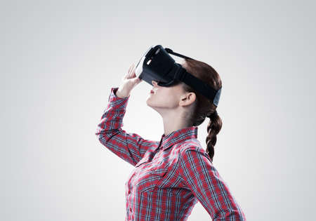 Young woman in checked shirt wearing virtual helmet against gray background
