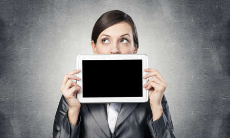 Businesswoman holding tablet computer with blank screen. Beautiful woman in business suit show tablet PC near her face. Corporate businessperson on grey wall background. Digital technology layout.