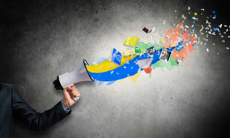 Businessman hand holding megaphone on wall background. Colorful paint splash flying out from loudspeaker. Event announcement and business advertisement. Social media broadcasting and online streaming 写真素材
