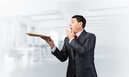 Scared businessman covering mouth with hand and holding open book. Startled adult man in business suit and tie standing on blurred office background. Education and knowledges. Business accounting