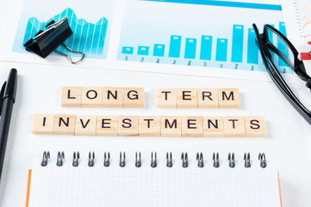 Long term investments concept with letters on wooden cubes. Still life of office workplace with supplies. Flat lay white surface with notepad, pen and financial report. Financial success and planning