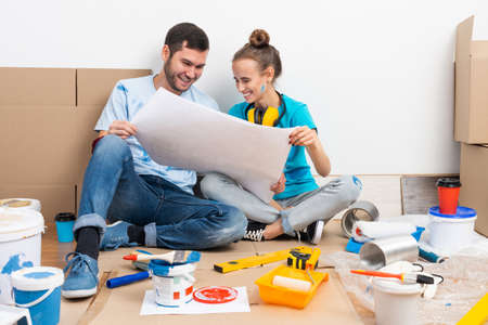 Happy couple sitting on floor with construction blueprint. Home remodeling and house interior redesign. Construction tools and materials lying on floor. Young family studies renovation project of flat Stok Fotoğraf