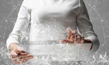 Businesswoman works with futuristic interface. Virtual geometric graphics with plexus effect and digital hologram. Double exposure concept of internet network communication. Cybernetic workspace