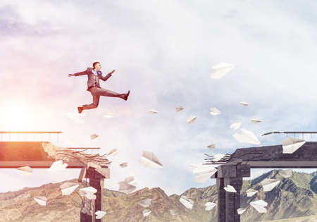 Businessman jumping over gap in bridge among flying paper planes as symbol of overcoming challenges. Skyscape with sunlight and nature view on background. 3D rendering.