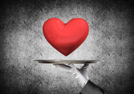Cropped image of waitresss hand in white glove presenting big red heart on metal tray with dark wall on background.