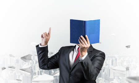 Businessman covered his face with organizer and finger pointing up. Man in business suit and tie standing on cityscape background with flying paper planes. Education and professional knowledges.