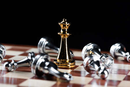 Gold queen chess defeats silver figures on wooden chessboard. Intellectual duel and tactical battle in business. Strategy planning, leadership and teamwork. Checkmate and winning in game concept.