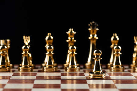Golden chess figures standing on chessboard. Intellectual and tactic game. Strategy planning, leadership and teamwork business concept. Close-up gold chess pieces in row on black background.