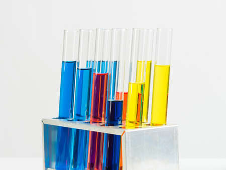 Science laboratory research and development. Modern biochemistry industry mockup. Close up test tubes with color liquid on white background. Chemical manufacture concept with glass equipment.