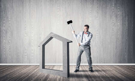 Determined businessman going to break with hammer house concrete figure