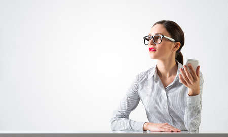 Smiling young woman sits at desk and dreamy looking upward. Portrait of beautiful girl in glasses with bright red lips on white wall background. Human resource and career development concept. Фото со стока