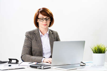 Attractive middle aged businesswoman working with computer in office. Business lady sitting at desk on white background. Successful corporate woman in suit and glasses posing at her workplace.