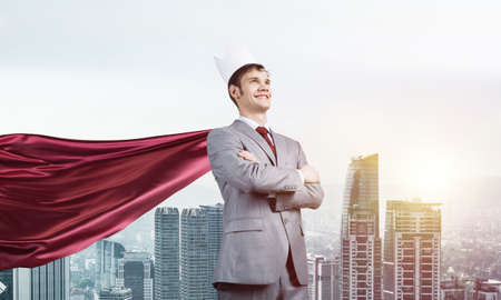 Young confident businessman wearing red cape against modern city background Фото со стока