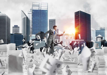 Businessman in suit running with phone in hand among flying papers with sunlight and cityscape on background. Mixed media.