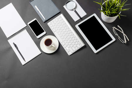 Top view of workplace with modern digital devices. Flat lay stylish design with black surface and copy space. Professional consulting, audit and accounting. Digital technology and mobile lifestyle.