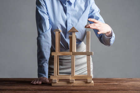 Business woman building construction on table from wooden blocks. Architecture engineering and construction. Company strategy planning, organization and development. Business motivation concept