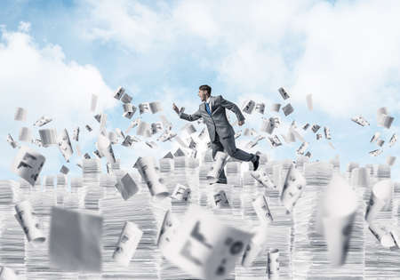 Businessman in black suit running with phone in hand among flying papers with cloudly skyscape on background. Mixed media. Фото со стока