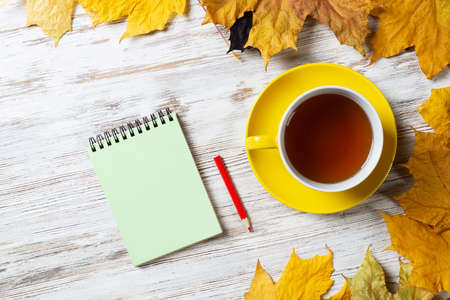 Flat lay autumn composition with cup of black tea and yellow autumn leaves. Time of tea break concept. Still life of hot drink and notepad with pen lies on vintage wooden desk with bright foliage.