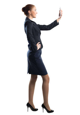 Young beautiful woman taking selfie photo with smartphone. Confident and stylish businesswoman in dark blue suit. Corporate businessperson isolated on white background. Mobile communication layout. Foto de archivo