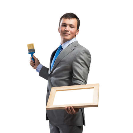Creative businessman painter holding paint brush and whiteboard in hands. Portrait of happy handsome man in business suit and tie isolated on white background. Ambitions and creativity in business. Imagens