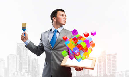Creative businessman painter holding paint brush and abstract 3d cube model. Complete solution and modern digital technology. Portrait of young man in business suit and tie on cityscape background. Imagens