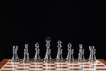 Silvery chess figures standing on chessboard. Intellectual competition and fight in business. Strategy planning and leadership concept with copy space. Silver chess pieces in row on black background. Foto de archivo