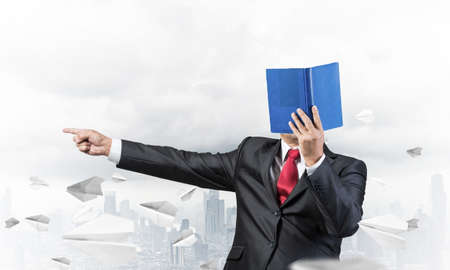 Businessman covered his face with organizer and finger pointing side. Man in business suit and tie standing on cityscape background with flying paper planes. Education and professional knowledges. Stockfoto