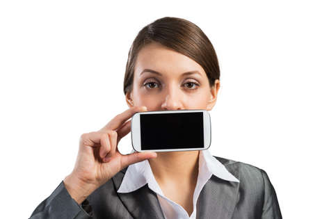 Portrait of young woman covering her mouth with smartphone. Businesswoman showing mobile phone with blank screen. Corporate businessperson isolated on white background. Mobile communication layout Stock fotó