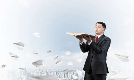 Serious businessman holding open book. Man in business suit standing on cloudy cityscape background with flying paper planes. Lawyer reading legal regulation book. Business accounting and consulting