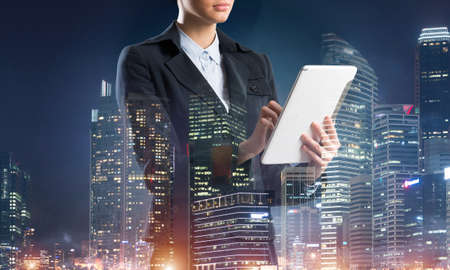 Businesswoman using tablet computer. Double exposure concept with night city and woman in business suit. Real estate investment. Digital technology in property management and development company.
