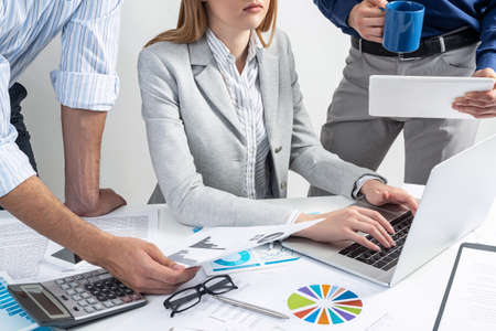 Business team working with documents. Secretary typing on laptop computer. Office desk with financial charts. Analysis of investment attractiveness and profit calculation. Business meeting in office