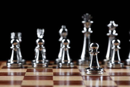 Steel chess figures standing on wooden chessboard. Intellectual duel and tactical battle in business. Strategy planning and leadership concept. Silver metal chess pieces in row on black background.