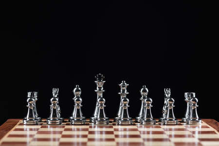 Silvery chess figures standing on chessboard. Intellectual competition and fight in business. Strategy planning and leadership concept with copy space. Silver chess pieces in row on black background. Archivio Fotografico