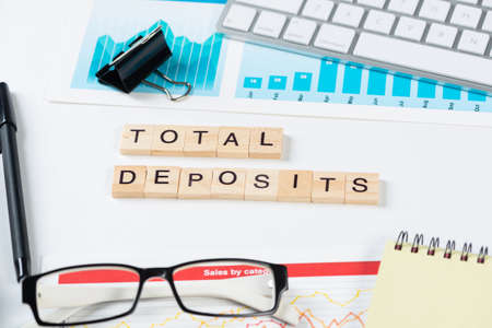 Total deposits concept with letters on wooden cubes. Still life of office workplace with supplies. Flat lay white surface with notepad, pen and financial report. Capital savings and banking.