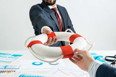 Business persons holding lifebuoy together. Business assistance and professional law consultation. Corporate teamwork and partnership. Insurance services for business. Independent audit and consulting