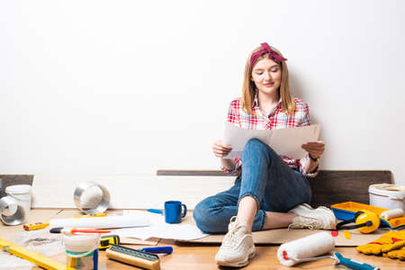 Happy pretty girl sitting on floor with paper blueprint. Home remodeling and house interior redesign. Construction tools and materials for building. Young woman studying renovation project of flat.