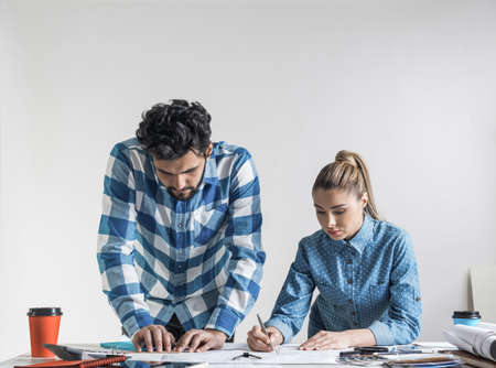 Young man and woman together working at design project. Creative teamwork at workspace with construction blueprint and color swatches. People standing near desk and discussing in architecture studio