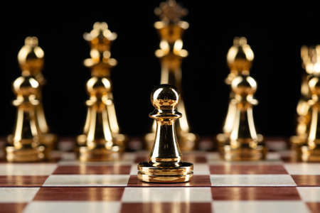 Golden chess figures standing on wooden chessboard. Intellectual duel and tactical battle in business. Strategy planning and leadership concept. Gold metal chess pieces in row on black background.