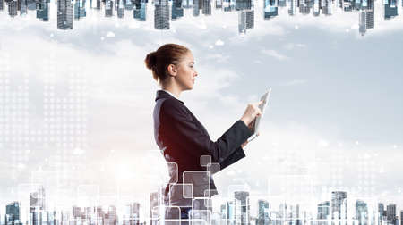 Young businesswoman with tablet computer on modern cityscape background. Double exposure concept with beautiful woman in business suit. Digital technology in stock trading and real estate investment