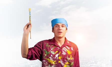 Handsome young painter artist pointing upwards with paintbrush in hand. Portrait of art school student in bandana on blue sky and cityscape background. Creative hobby and artistic occupation.