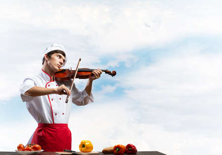 Young male chef with violin standing near cooking table with vegetables. Handsome chef in white hat and red apron on blue sky background. Creative culinary performance. High cooking skills concept Reklamní fotografie
