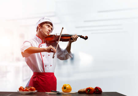 Young male chef with violin standing near cooking table with vegetables. Handsome chef in white hat and red apron in light kitchen interior. Creative culinary performance. High cooking skills concept Reklamní fotografie