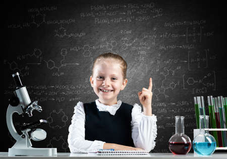 Little girl scientist sitting at desk in elementary science class. Research and education in school. Chemical laboratory with microscope, flasks and test tubes. Happy schoolgirl finger pointing up