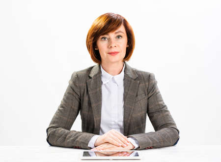 Attractive middle aged businesswoman sitting with folded arms. Concentrated business lady at desk on background of white wall. Successful corporate woman in suit posing at her workplace in office. Foto de archivo