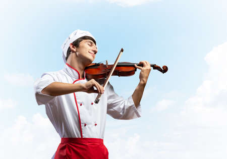 Young male chef playing violin on blue sky background. Handsome chef in white hat and red apron standing with music instrument. Creative culinary performance. High cooking skills concept Reklamní fotografie