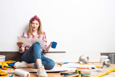Beautiful woman sitting with paper blueprint in hand. Home remodeling and house interior redesign. Young woman studying renovation project of flat.
