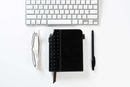 Still life of modern office workspace with supplies. Flat lay white desk with organizer notebook and computer keyboard. Time management and day planning concept. Blank notebook page for message.