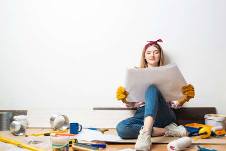 Happy woman sitting on floor with paper blueprint. Home remodeling after moving. Construction tools and materials for building.