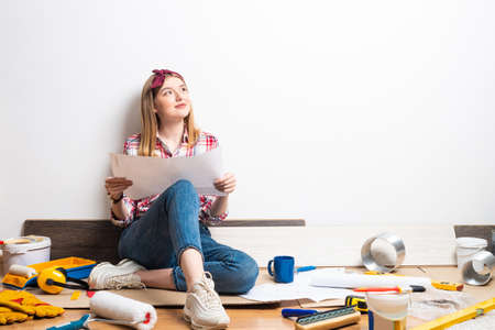 Interior designer studying renovation project. Smiling pretty girl sitting on floor with paper blueprint. Home remodeling and house interior redesign. Standard-Bild